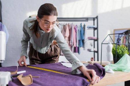 Näherin misst Tuch in der Nähe von Nähmustern und Maschine im Atelier
