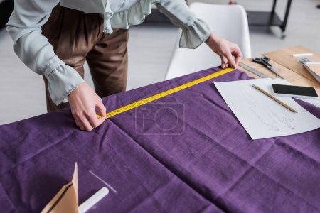 Photo pour Vue recadrée du tissu de mesure de couturière près du téléphone cellulaire et croquis - image libre de droit