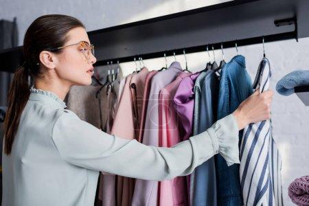Photo pour Vue latérale de la jeune couturière regardant les vêtements sur le cintre - image libre de droit
