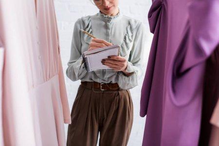 Photo pour Vue recadrée de couturière écrivant sur carnet près des vêtements au premier plan flou - image libre de droit