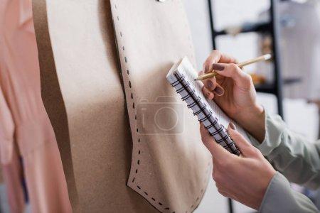 Photo pour Vue recadrée de couturière écrivant sur carnet près de motifs de couture en atelier - image libre de droit
