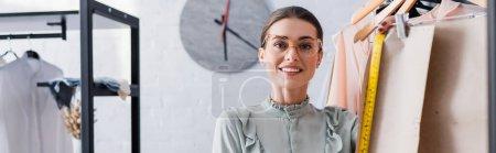 Photo pour Designer souriant regardant la caméra près des motifs de couture sur les cintres, bannière - image libre de droit
