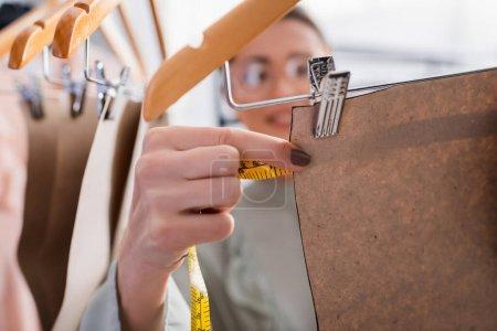 Photo pour Designer flou mesurant le motif de couture sur cintre en atelier - image libre de droit