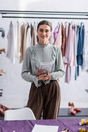 Photo pour Joyeux couturière tenant cahier près de tissu flou - image libre de droit