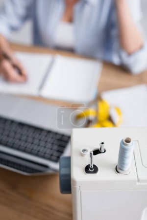 Cropped view of sewing machine near blurred seamstress and laptop