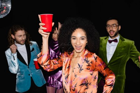Photo for Positive african american woman with toasting gesture on party with multiracial friends on black background - Royalty Free Image