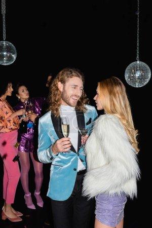 lächelndes Paar spricht auf Party mit multirassischen Freunden auf schwarzem Hintergrund