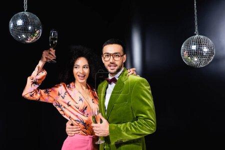 Photo pour Positif couple multiracial boire du champagne sur fond noir - image libre de droit