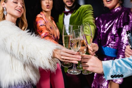 interracial friends in stylish clothes clinking with glasses of champagne on black background