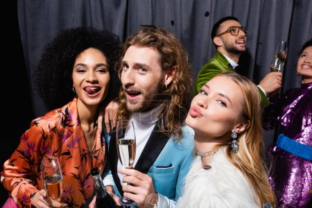 Photo for Interracial friends in stylish clothes grimacing and drinking champagne near grey curtain on black background - Royalty Free Image