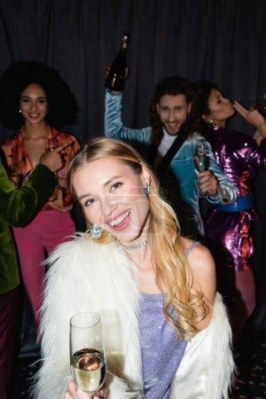 lächelnde junge erwachsene blonde Frau mit einem Glas Champagner auf einer Party mit interrassischen Freunden auf grauem Hintergrund