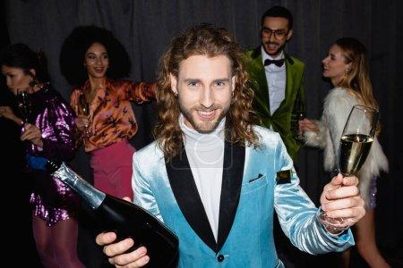 Photo pour Jeune homme adulte souriant tenant un verre et une bouteille de champagne près d'amis danseurs flous en arrière-plan - image libre de droit