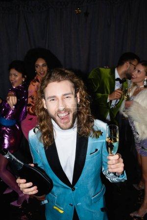 positiver Mann tanzt mit gemischtrassigen Freunden in bunten Klamotten in einem Nachtclub auf grauem Hintergrund