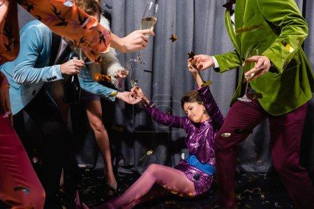 betrunken asiatische junge erwachsene Frau sitzt auf dem Boden unter interrassischen Freunden auf grauem Hintergrund
