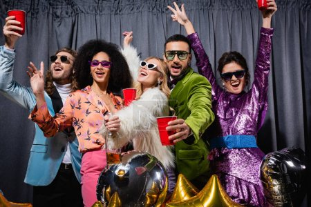 Photo for Smiling interracial friends in sunglasses having party on grey background - Royalty Free Image