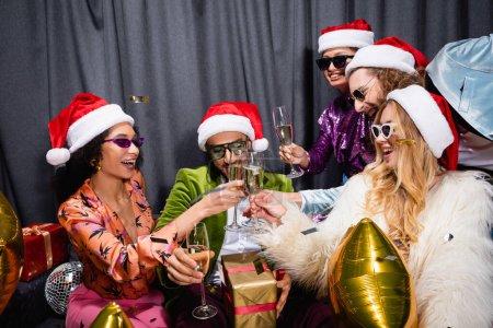 Photo pour Heureux interracial amis dans santa chapeaux et lunettes de soleil cliquetis avec des lunettes sur canapé gris sur fond gris - image libre de droit