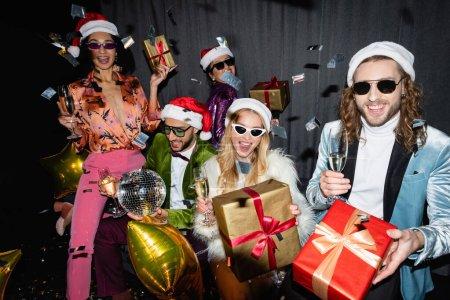 Photo pour Souriant interracial amis dans santa chapeaux et lunettes de soleil ayant fête près de rideau gris sur fond noir - image libre de droit
