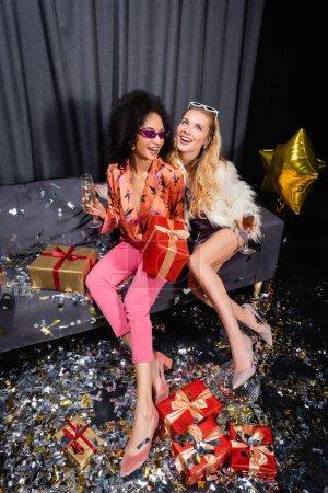 lächelnde junge erwachsene interrassische Frauen sitzen mit Champagner auf einer grauen Couch in der Nähe eines Vorhangs auf schwarzem Hintergrund