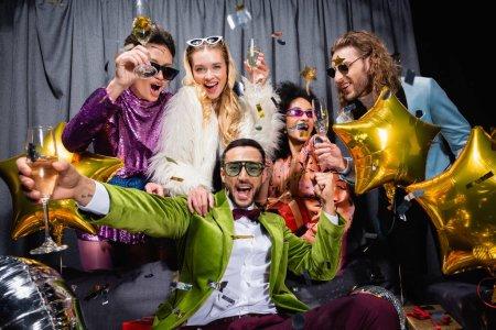 positive interrassische Freunde in Sonnenbrille und farbenfroher Kleidung, die Champagner in der Nähe des grauen Vorhangs auf schwarzem Hintergrund trinken