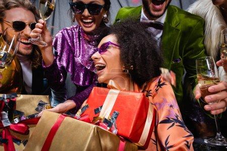 lächelnde afrikanisch-amerikanische Frau mit Geschenkschachteln sitzt unter interrassischen Freunden auf grauem Hintergrund