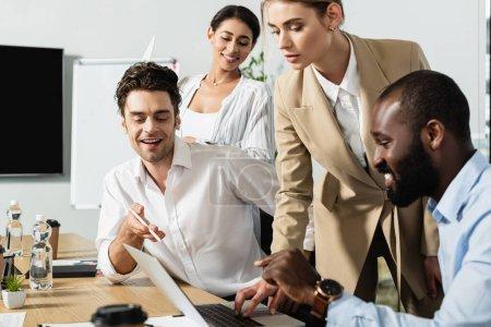 Photo pour Des partenaires d'affaires interraciaux souriants pointant vers un ordinateur portable dans une salle de conférence - image libre de droit
