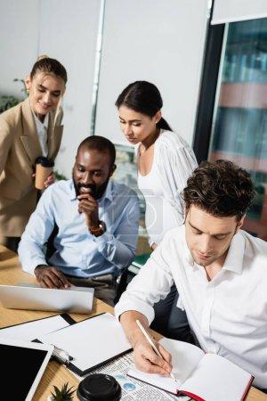 Photo pour Homme d'affaires écrit dans un carnet près de collègues interracial travaillant sur fond flou - image libre de droit