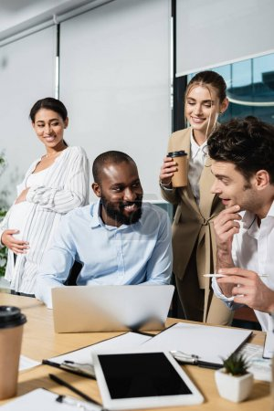 Photo for African american businessman smiling near laptop and positive colleagues during meeting - Royalty Free Image