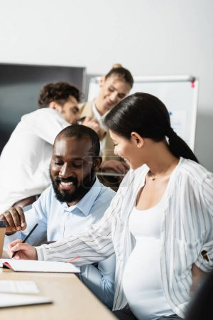 Photo for Pregnant businesswoman writing in notebook near african american colleague and blurred coworkers - Royalty Free Image
