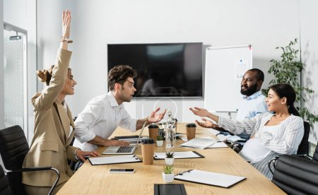 excited multiethnic business people gesturing during discussion in conference room