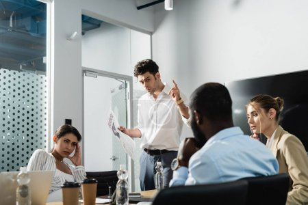 businessman with newspaper showing idea gesture near multiethnic coworkers