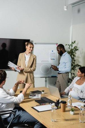 Photo pour Femme d'affaires souriante montrant presse-papiers avec des graphiques à ses collègues - image libre de droit