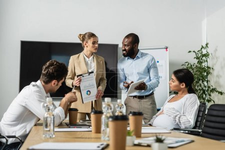 Photo pour Homme d'affaires afro-américain pointant vers tablette numérique lors d'une discussion avec des collègues multiethniques - image libre de droit
