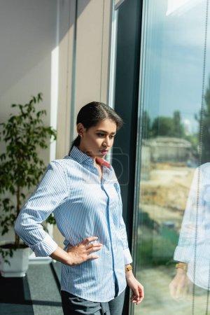 Foto de Pensativa mujer de negocios afroamericana de pie cerca de la ventana con la mano en la cadera - Imagen libre de derechos