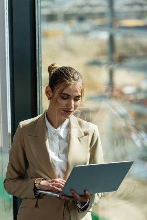 junge Geschäftsfrau steht mit Laptop am Fenster im Büro