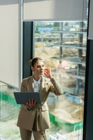Photo for Dreamy businesswoman holding laptop while looking away through window in office - Royalty Free Image