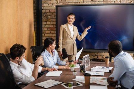 Photo pour Femme d'affaires pointant vers lcd moniteur près de collègues multiethniques lors de la réunion - image libre de droit