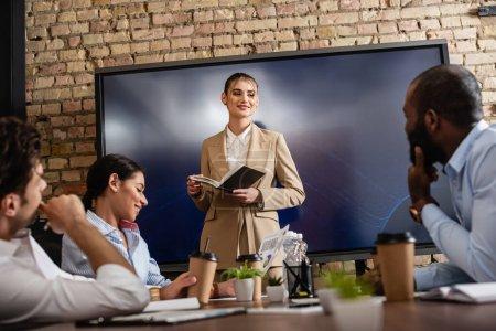 Photo pour Jeune femme d'affaires avec ordinateur portable debout près des partenaires d'affaires interracial dans la salle de conférence - image libre de droit