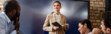 Photo for Smiling businesswoman standing with notebook near interracial colleagues, banner - Royalty Free Image
