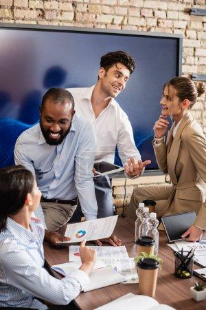 Photo pour Des hommes d'affaires interraciaux souriants parlant pendant une réunion en salle de conférence - image libre de droit