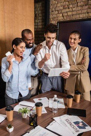 personas de negocios multiculturales emocionados mostrando gesto de éxito cerca de colega con tableta digital