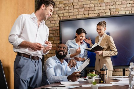 positive interracial businesspeople talking in conference room