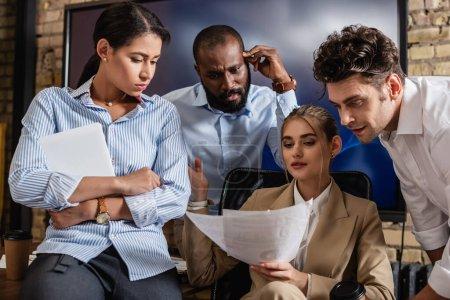 Photo pour Femme d'affaires détenant des documents près de collègues interracial réfléchis dans la salle de conférence - image libre de droit