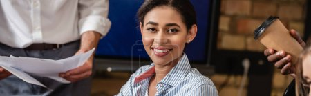 happy african american businesswoman smiling at camera near colleagues, banner