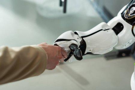 Photo pour Vue partielle d'une femme d'affaires serrant la main d'un robot au bureau - image libre de droit