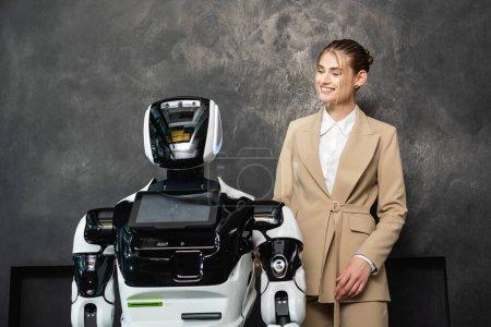 Photo pour Joyeuse femme d'affaires debout près du robot dans le bureau - image libre de droit