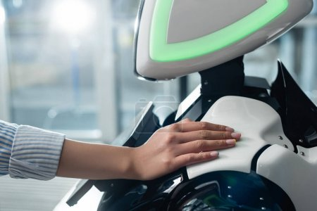 Photo for Cropped view of female hand touching robot in office - Royalty Free Image