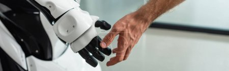 Photo for Partial view of engineer touching hand of humanoid robot, banner - Royalty Free Image