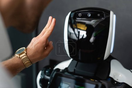 Photo for Cropped view of businessman showing victory gesture near robot in office - Royalty Free Image