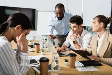 Photo pour Homme d'affaires afro-américain pointant vers un ordinateur portable près de collègues multiethniques - image libre de droit