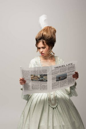 Photo for Worried woman in elegant retro dress reading travel life newspaper isolated on grey - Royalty Free Image